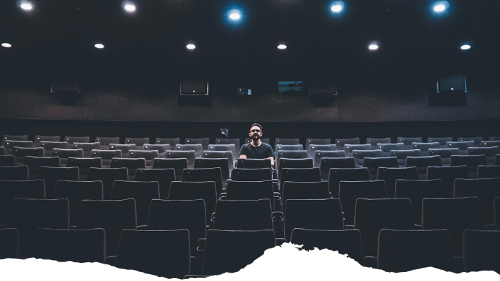 A man sits in an empty theater, illustrative of event closures from the COVID-19 pandemic.