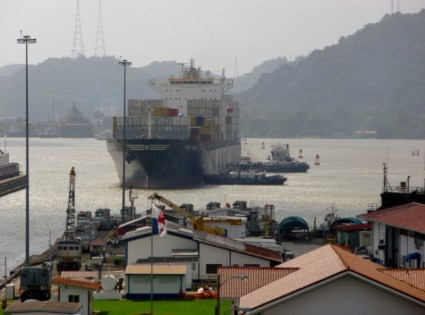tugs maneuver ship into the Panama Canal