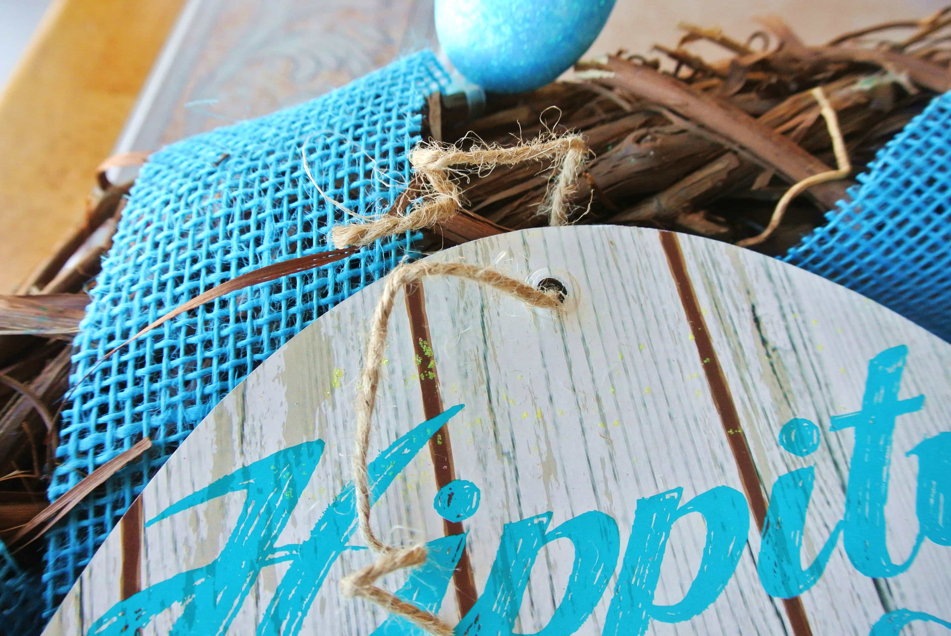 Untie loop of Easter sign. Weave the string through 2-3 grapevine pieces and fasten tightly.