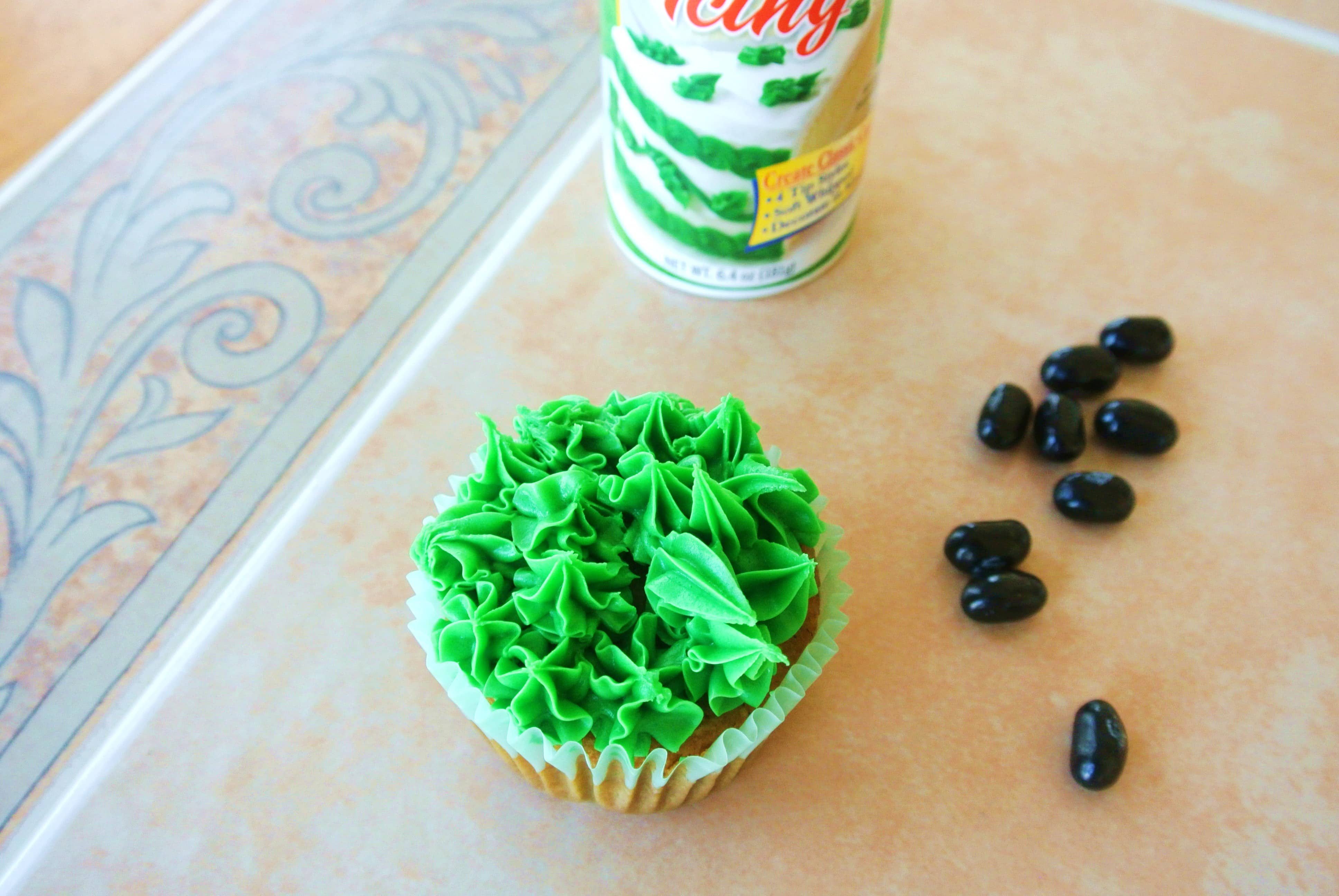 Decorating Bunny Poop Cupcakes with green icing and black jelly beans