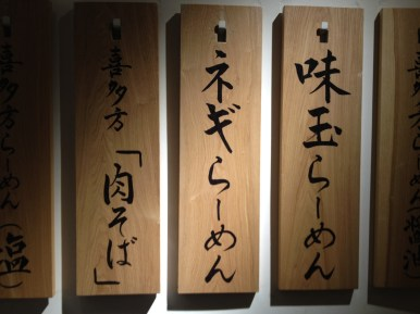 The menu is displayed on wooden boards outside of the store (Shichisai Menya in Tokyo Station)