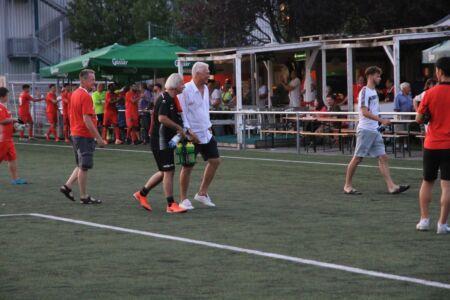 Trainer und Spieler gehen über den Fußballplatz Richtung Kabine