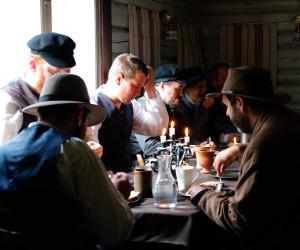 The men, eating breakfast, separate from the women (Play, Simon Svensson)