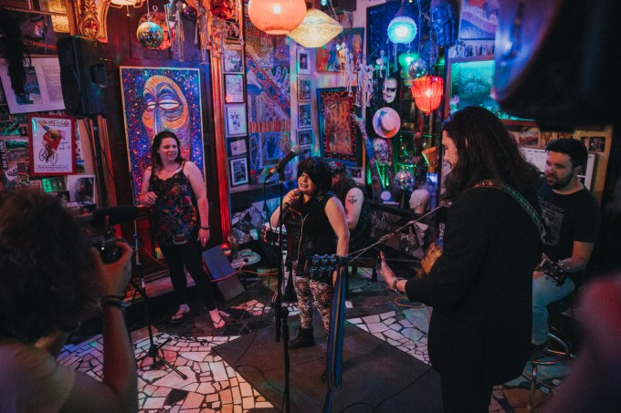 Four musicians play in a venue with multicolored lights