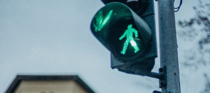 Crossing lamp with green illuminated person walking and a building in the background