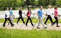 Photo d'un groupe (hommes et femmes) pratiquant la marche nordique sur un large chemin, au bord d'un lac du Bois de Vincennes à Paris.