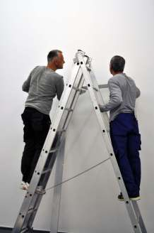 Teamarbeit: Zwei Techniker, eine Leiter.
