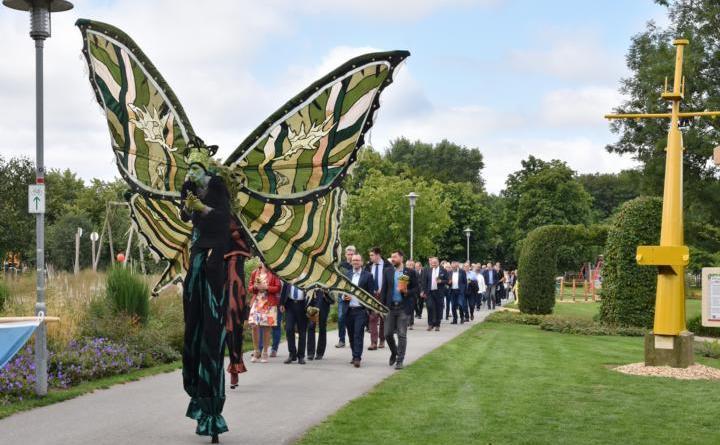 Stelzenläufer und Fahnenträger gingen den rund 250 Besuchern bei der Eröffnung der Blumenschau 2019 voran. Am Mittwochvormittag wurde die Hauptveranstaltung der Blumenschau im Stadtpark feierlich eröffnet. Bild: Ute Müller