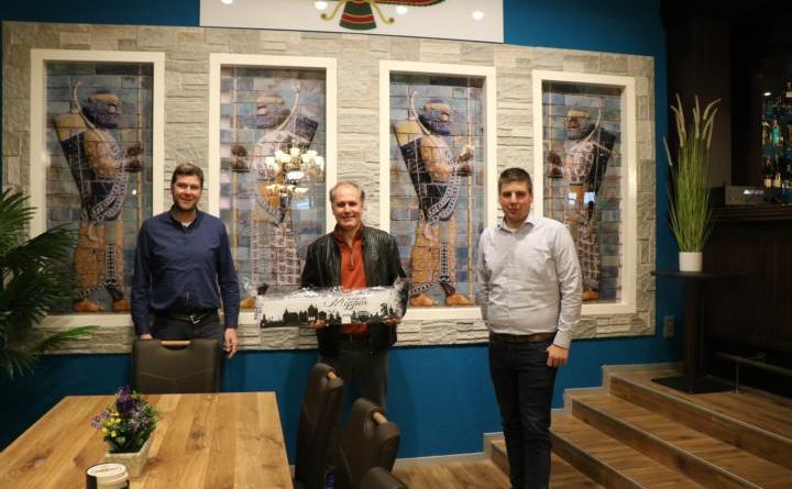 """Frank Thole, Geschäftsführer der Tourist Information TIM e.V. (links) und Alexander Kassner, Wirtschaftsförderer der Stadt Meppen, gratulierten Gastronom Bahman Bayat (Mitte) und seinen Mitarbeitenden zur Neueröffnung und übergaben die """"Meppener Skyline"""". Foto: Stadt Meppen"""