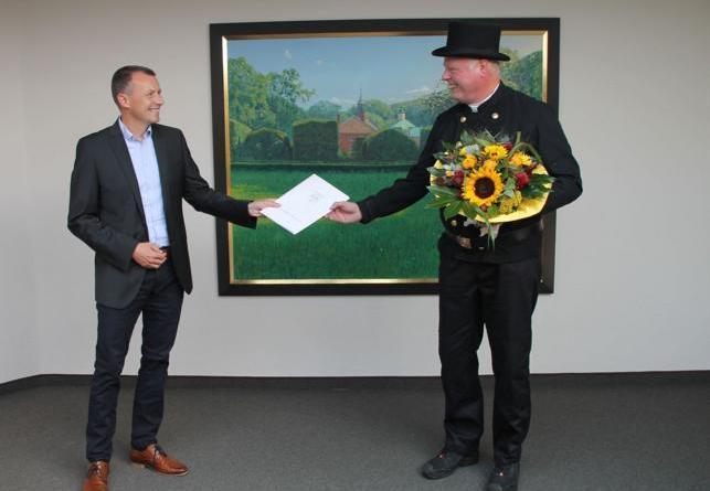 Dezernent Michael Steffens (links) ehrt den Schornsteinfeger Klaus Holterhaus (r) im Meppener Kreishaus. (Foto: Landkreis Emsland)