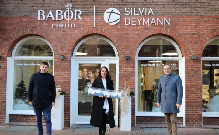 """Wirtschaftsförderer Alexander Kassner (links) und Bürgermeister Helmut Knurbein (rechts) gratulierten Silvia Deymann (Mitte) zur Neueröffnung ihres Kosmetikstudios und überreichten als Geschenk die """"Meppener Skyline"""". Foto: Stadt Meppen"""