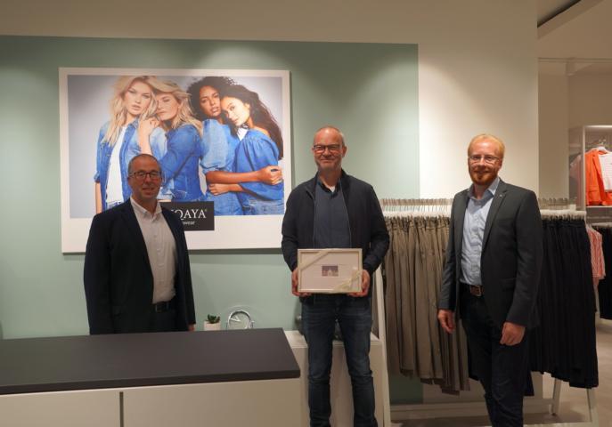 """Citymanager Andreas Löpker (links) und Marko Schnitker, stellvertretender LWT-Geschäftsführer, (rechts) gratulieren Michael Mönstermann zur Neueröffnung von """"Minqaya Womenswear"""" in Lingen. Foto: Stadt Lingen"""