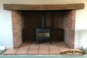 Consort 9 Wood Burner with a large oak beam and pamment hearth.