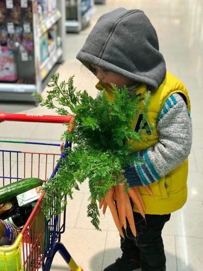 Plastikfrei einkaufen – Merlin trägt ein schweres Bund Karotten