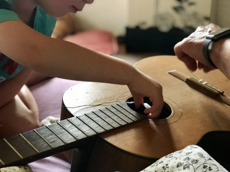 Klimaschutz – Junge zieht neue Saiten auf eine alte Gitarre