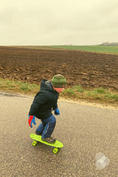 Merlin übt Skateboard fahren im Winter