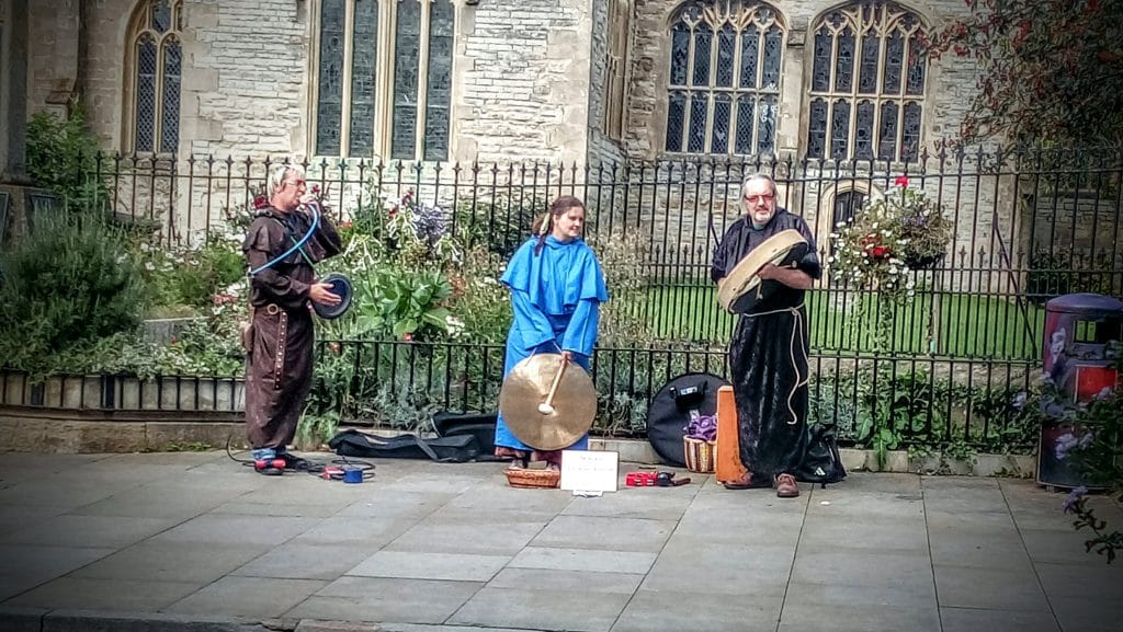 Buskers dressed as monks outside St John's Church, Glastonbury