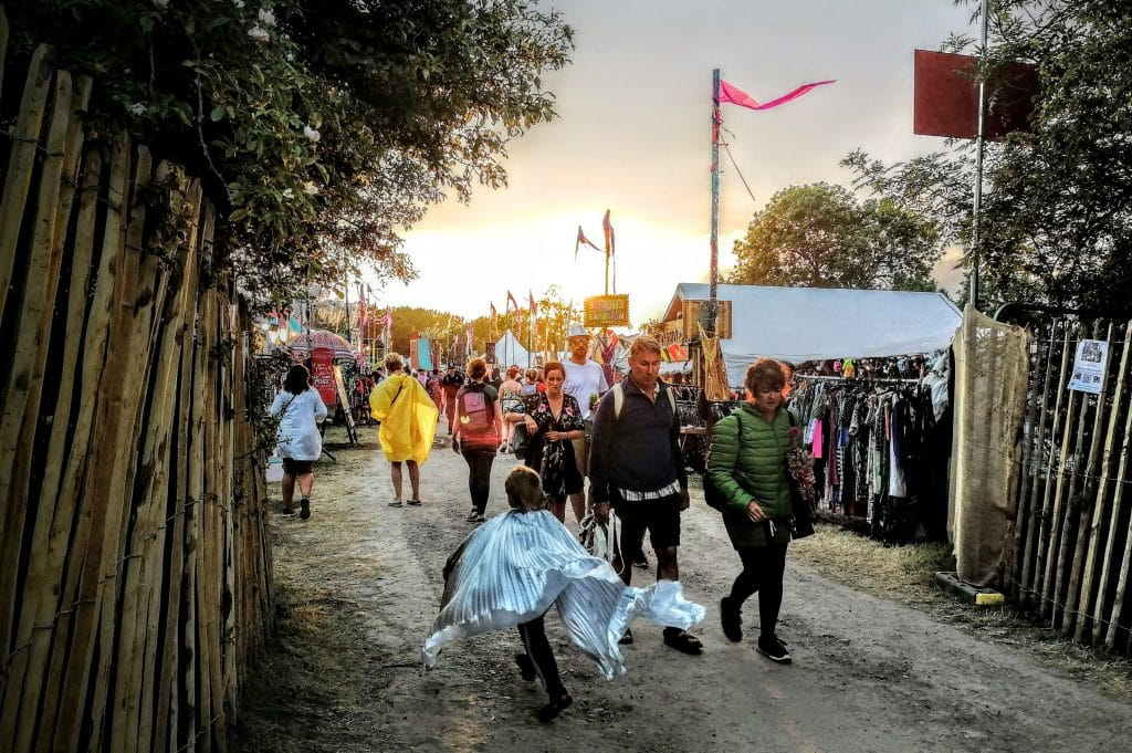 Sunset at Glastonbury Festival 2019, a small boy in a metallic cape