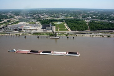 A barge travels down the Mississippi, looking into Illinois from the top of the Arch
