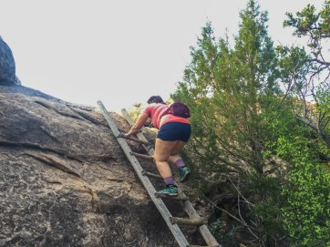 Climbing one of the ladders up the rock formation