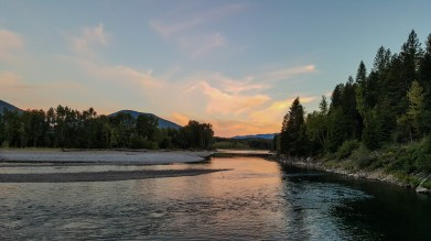 A pink and orange sunset over calm, still water of the North Fork of the Flathead River in Glacier National Park