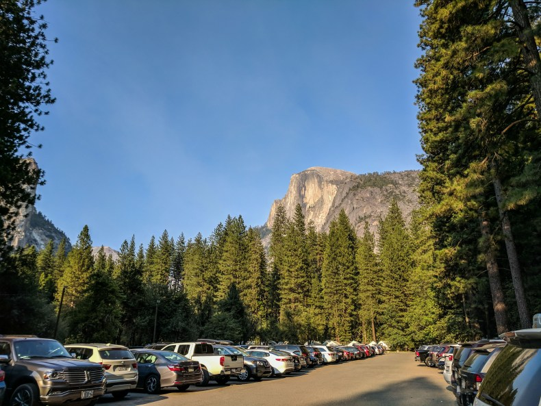 A full parking lot with Half Dome looming in the distance in Yosemite National Park