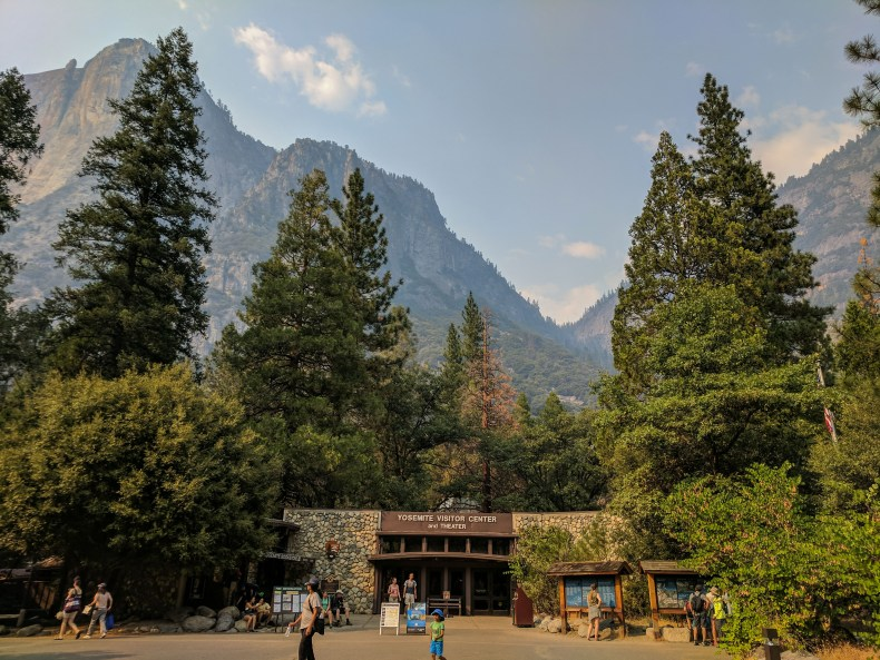 Yosemite Valley Visitor Center in foreground where UNESCO World Heritage Site plaque is located with Lost Arrow and Yosemite Point above
