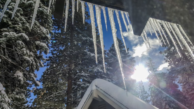Long icicles hang from the edge of a house with snow covered pine trees and sunshine in the background