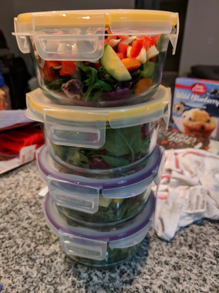 A tall stack of salads in Tupperware