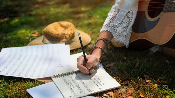 Woman writing words while holding guitar.,