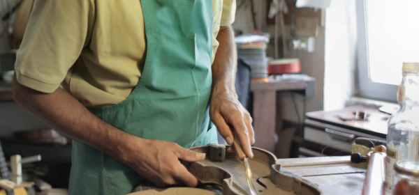 crop male artisan cutting violin from tree in workplace