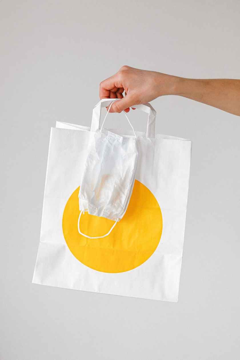 person holding paper bag and face mask