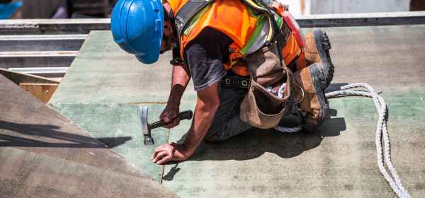 man wearing blue hard hat using hammer