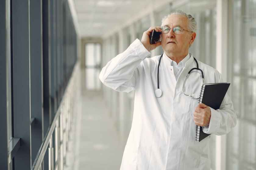 serious doctor in medical uniform talking on cellphone in clinic
