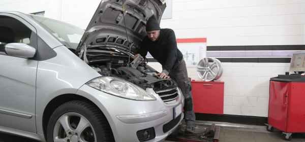man in black jacket standing beside silver car