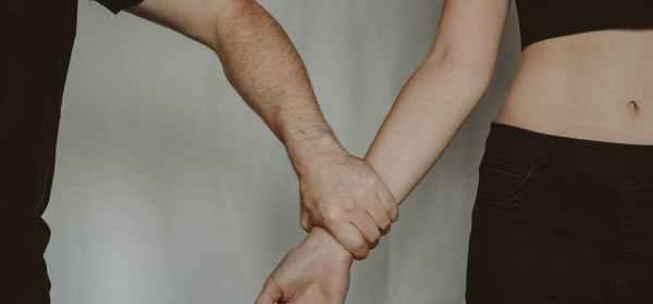 crop man grasping hand of woman