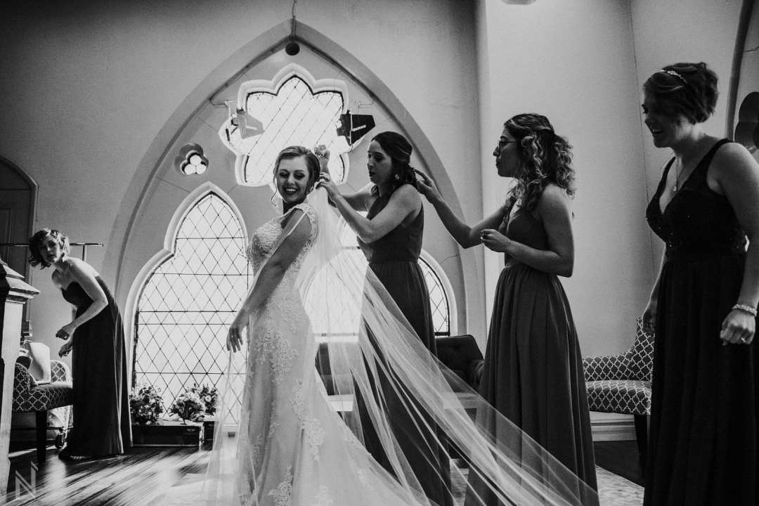 Bridal portraits in lace wedding gown with long train and cap sleeves at St. Francis Xavier Church in St. Louis, MO