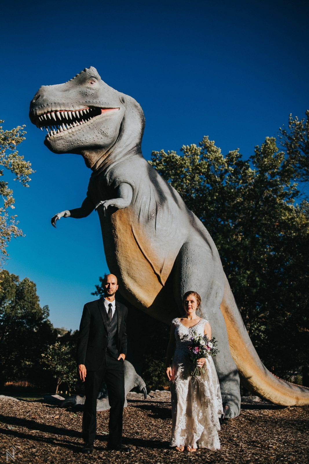 Bride and Groom picture in front of T Rex statue outside of the Science Center in St. Louis, MO