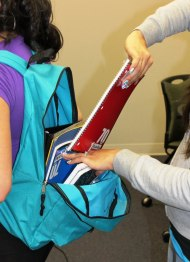 Volunteers stuff backpacks for the upcoming school year.