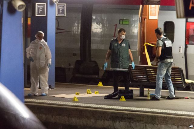 Police officers conduct their investigation on an Amsterdam-to-Paris train after a gunman wounded three people before being overpowered, at Arras station, northern France, Aug. 21, 2015.