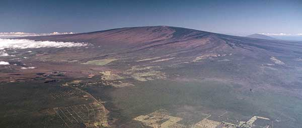 USGS Hawaiian Volcano Observatory scientists are closely monitoring recent signs of unrest on Mauna Loa, the largest active volcano on Earth. In this 1985 aerial photo, Mauna Loa looms above Kīlauea Volcano's summit caldera (left center) and nearly obscures Hualālai in the far distance (upper right).