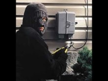 A burglar cutting a phone line.