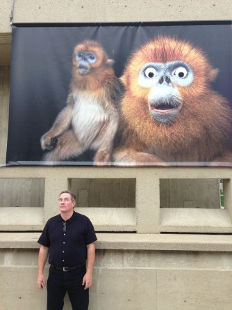"Joel Sartore posing with one of his posters on campus that was defaced with ""googly eyes."" Photo Courtesy of Evan Sgouris"