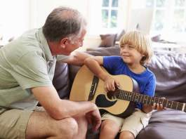Grandfather Teaching Grandson To Play Guitar