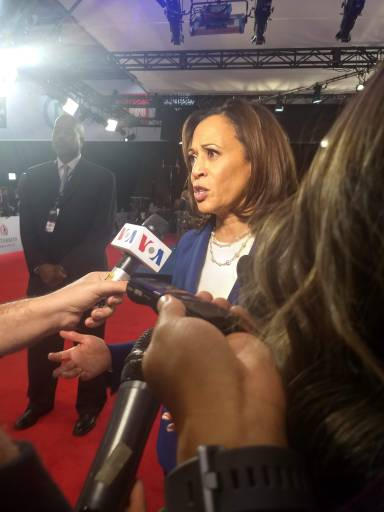Kamala Harris talking with a Voice of America in front of her.