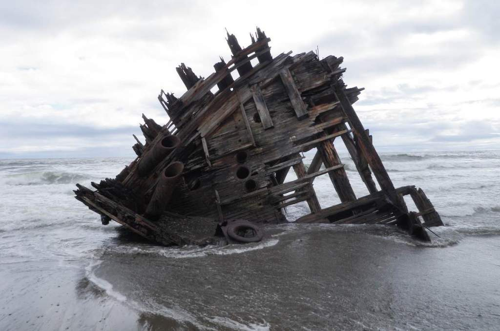 A shipwreck on a sandy beach where only the hull of the wooden ship is left and it's sinking into the wet sand. The sky and ocean in the background are grey.