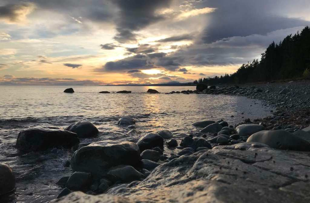 Looking out to the ocean from a rocky beach with a large rock in the foreground. The sky is a grey, twilight colour with an orange setting sun on the horizon and there are tall evergreens in the distance to the right.