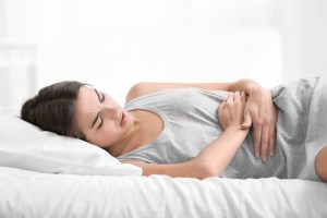 woman laying on bed experiencing menstrual pain