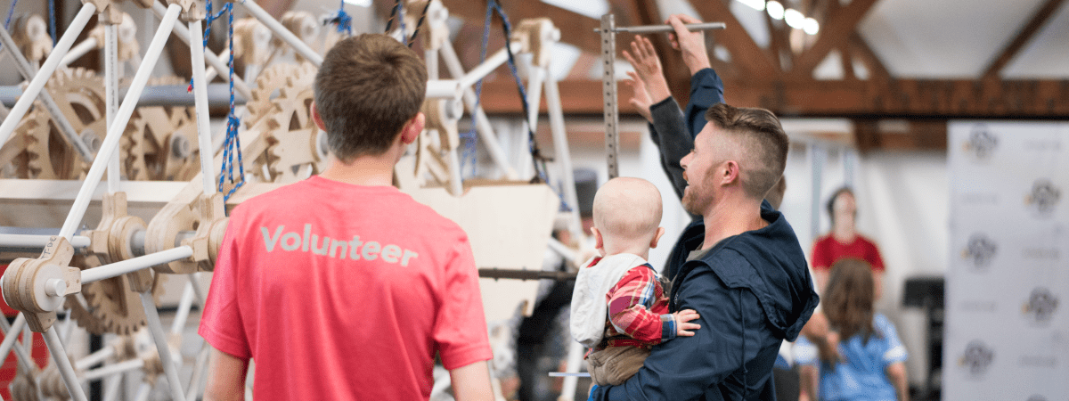 Two men and a baby examine the Arkansas Strandbeest at the Maker Faire North Little Rock.