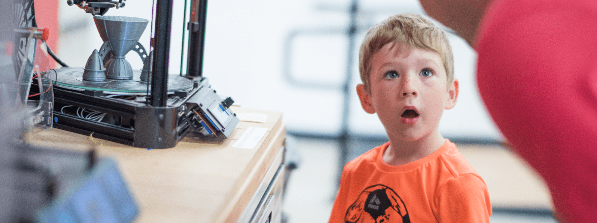A young boy stands in awe watching a 3D printer print a rocket.